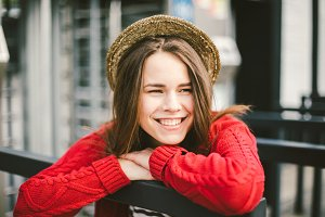 beautiful young girl smiling, is happy, happy in a hat, a red shirt over city