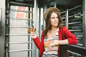 beautiful young girl in the city in the red sweater, hat, white clock, on the background of metal structures