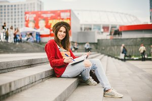 A beautiful, young Caucasian girl sitting on the street smile, the joy, sit with notebook and pen in Ruhi. In the red sweater, jeans and brown leather bag