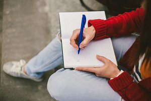 beautiful girl sitting on the street with a notebook and pen in hand, making notes and rests.