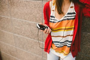 beautiful girl listening to music with headphones holding a smart phone, the player in the hand. Dressed in a red jacket and jeans.