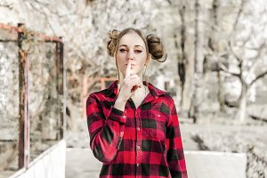 The young girl covers her mouth with her finger. A gesture of silence