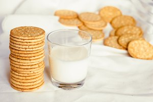 A glass of milk with a biscuit biscuit