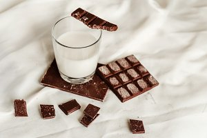 Fresh milk in a glass cup and milk chocolate in tiles