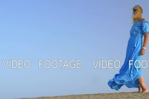 Slow motion view of young blond woman standing against blue sky in long blue dress and it is fluttering on the wind