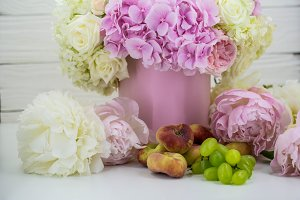 beautiful peonies in the pink box with fruits on wooden background
