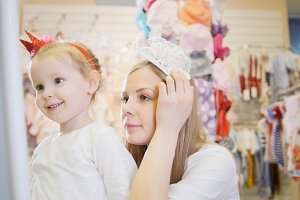 Children shopping - mom tries on a white headband next to his daughter
