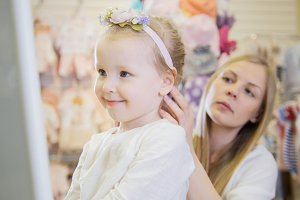 Mother clothes daughter accessoriesnear mirror