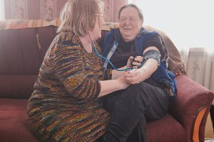 The neighbor measures the elderly woman's blood pressure