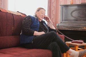 An elderly woman speaks phone at home