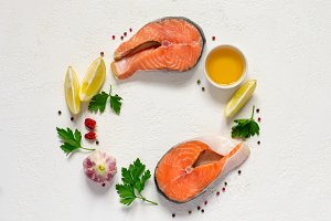 Fresh raw salmon steak, olive oil, lemon and spices are arranged