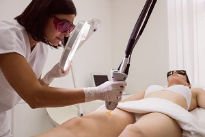 Doctor performing laser hair removal on female patient skin