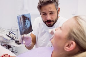 Dentist showing x-ray to the patient