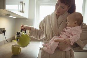 Loving mother carrying baby while making coffee