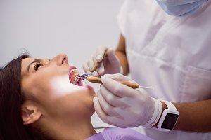 Dentist examining female patient teeth