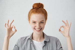 Everything is just fine! Cheerful excited young Caucasian female with ginger hair knot and freckled skin showing Ok gesture with both hands and smiling broadly, enjoying her carefree happy life