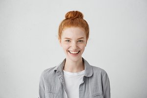 Close up portrait of cute redhead European student girl with hair knot and clean freckled skin looking at camera with happy expression, having fun indoors, relaxing after morning lectures at college