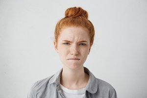 Portrait of unhappy young European ginger female with freckles all over her face looking at camera, having painful eyes, biting lower lip as if trying to relieve pain. Human emotions and feelings