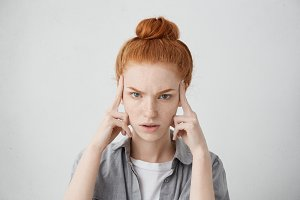 Close up shot of stressed unhappy young Caucasian woman wearing her ginger hair in bun, keeping fingers on temples, suffering from severe headache, migraine or trying hard to recollect something