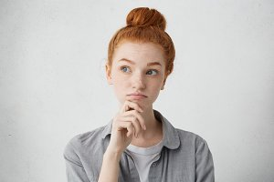 Portrait of charming young red haired lady looking away with doubtful expression, holding hand on her chin while thinking over alluring interesting job proposal, weighing up all pros and cons