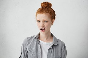 What? Indignant young beautiful woman with hair knot dressed in casual clothing standing at grey studio wall, grimacing, expression her dislike or disregard, feeling unwillingness towards something