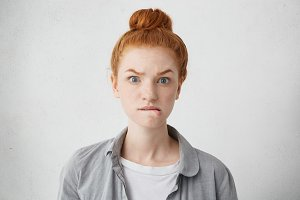 Headshot of anxious redhead freckled Caucasian girl raising eyebrows and biting lower lips having scared, nervous or angry look, waiting for something with impatience, posing isolated in studio