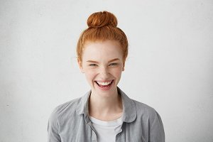 Human facial expressions, emotions, feelings, reaction and attitude. Cheerful redhead European girl with freckles laughing happily, showing her white teeth while watching good comedy show on TV
