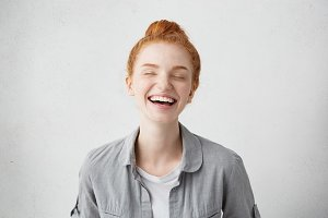 Youth, happiness, people and lifestyle concept. Studio shot of attractive joyful young European woman with ginger hair and freckles all over her face, smiling widely, closing eyes with pleasure