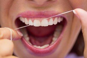 Female patient flossing her teeth