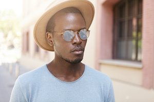 Close up urban shot of attractive Afro American man wearing t-shirt, hat and mirror lens shades having walk along streets of small town on sunny day while spending weekends abroad. People and travel