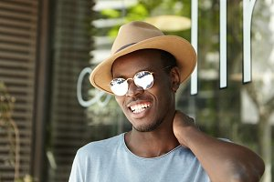 People and urban lifestyle. Outdoor portrait of carefree relaxed young dark-skinned European man in beige hat and stylish sunglasses smiling happily and rubbing his neck, having lunch at sidewalk cafe