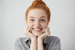 Tell me more. Close up shot of curious 20 y.o. redhead Caucasian woman pillowing face on her hands and looking at camera with anticipation and excitement while listening to story or gossips