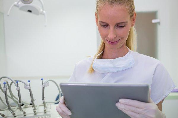 Female dentist using a digital tabl…