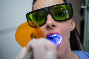 Dentist examining patients teeth with dental curing light