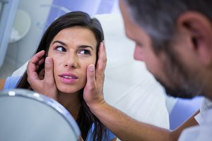 Doctor checking patients skin after cosmetic treatment