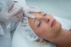 Female patient receiving a botox injection on forehead