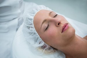 Patient lying on bed while receiving cosmetic treatment