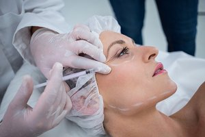 Woman with marked face receiving botox injection