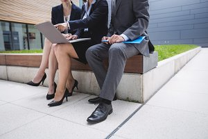 Businesswoman sitting with colleagues and using laptop
