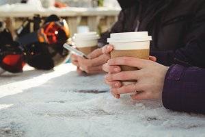 Couple with coffee cup using mobile phone