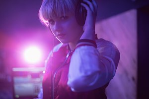 Portrait of female dj listening to music in headphones