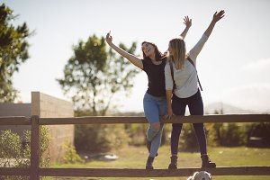 Friends taking selfie on mobile phone in farmland