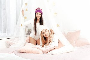 Beautiful two girls having fun in bedroom