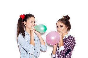 happy girls inflate colored balloons