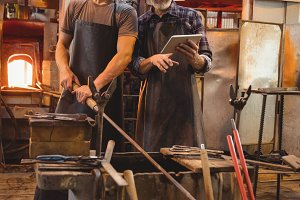 Team of glassblowers using digital while working over a molten glass