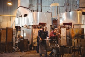 Team of glassblower shaping a glass on the blowpipe