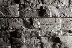 Gray brick background with shadows.