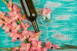 Bottle of wine and wineglass with light pink gladiolus on the azure background
