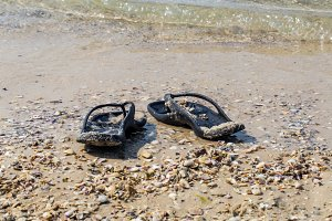 black flip flops on the beach, summer vacations