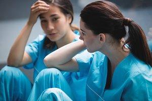 Sad nurses sitting on corridor